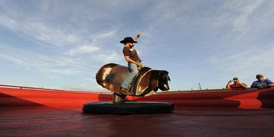 Payton Bayer rides a mechanical bull during the 13th Annual Margarita and Salsa Festival at the Heart O' Texas Fair Complex in Waco, Texas August 23, 2008. REUTERS/Jonathan Ernst   (UNITED STATES) - RTR21N2Y